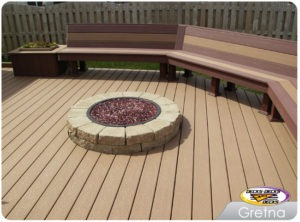 A low maintenance deck with a bench and fire pit built in
