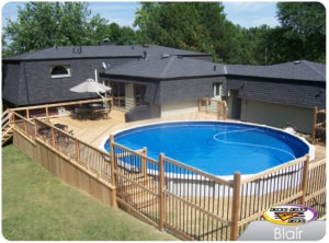 A low maintenance pool deck with a table, chairs, and umbrella